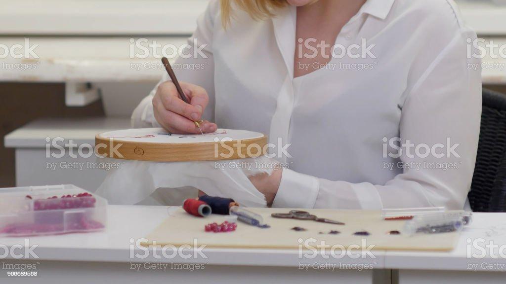 Mãos de mulher bordadeiras com gancho de luneville na seda - foto de acervo