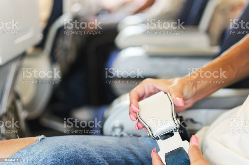 Woman hands fasten belts in airplane stock photo