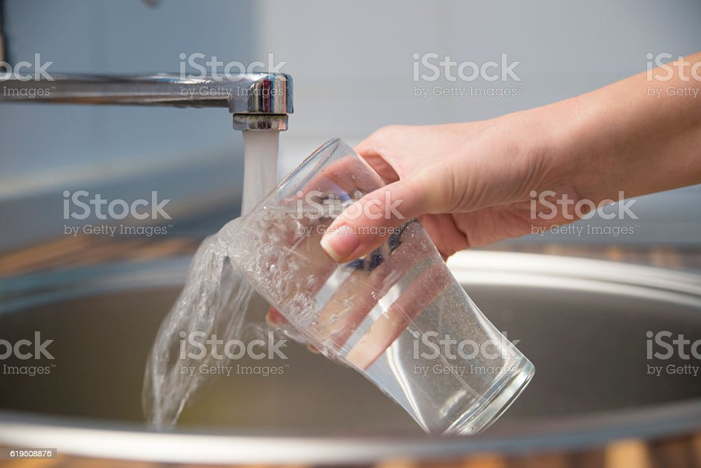 Woman hand's filling the glass of water. stock photo