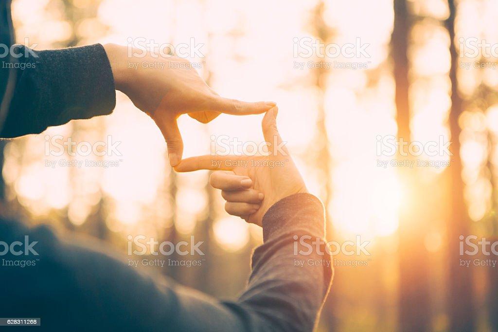 Woman hands framing far sunlight stock photo