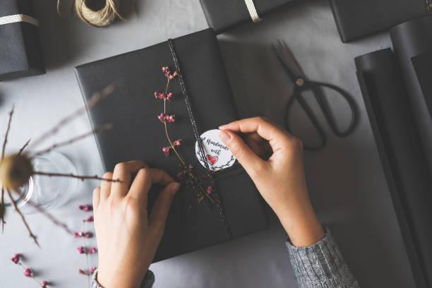 frau hände geschenkpapier weihnachten präsentiert - bastelkarton stock-fotos und bilder