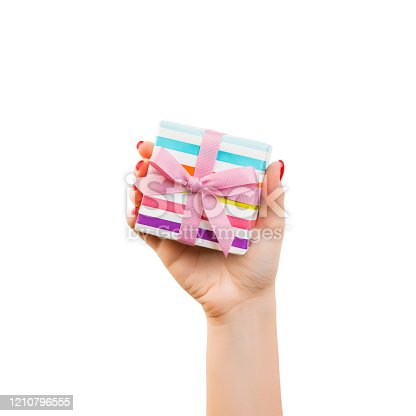 Woman hands give wrapped Christmas or other holiday handmade present in colored paper with pink ribbon. Isolated on white background, top view. thanksgiving Gift box concept.