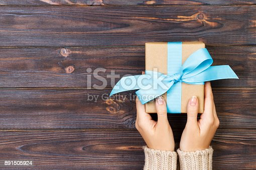 istock Woman hands give wrapped valentine or other holiday handmade present in paper with blue ribbon. Present box, decoration of gift on white wooden table, top view with copy space 891505924
