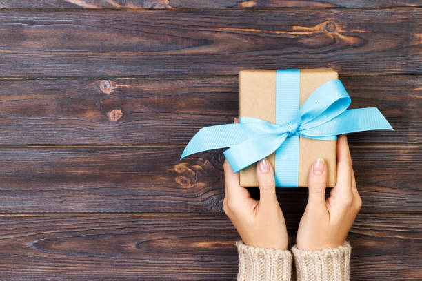 Woman hands give wrapped valentine or other holiday handmade present in paper with blue ribbon. Present box, decoration of gift on white wooden table, top view with copy space stock photo