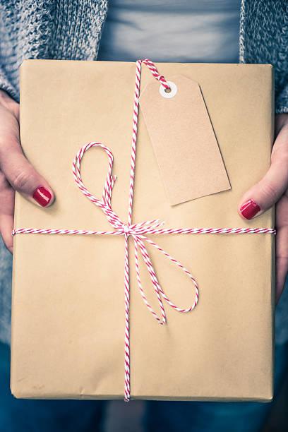 woman hands hold book for christmas present - basteln mit zeitungspapier stock-fotos und bilder