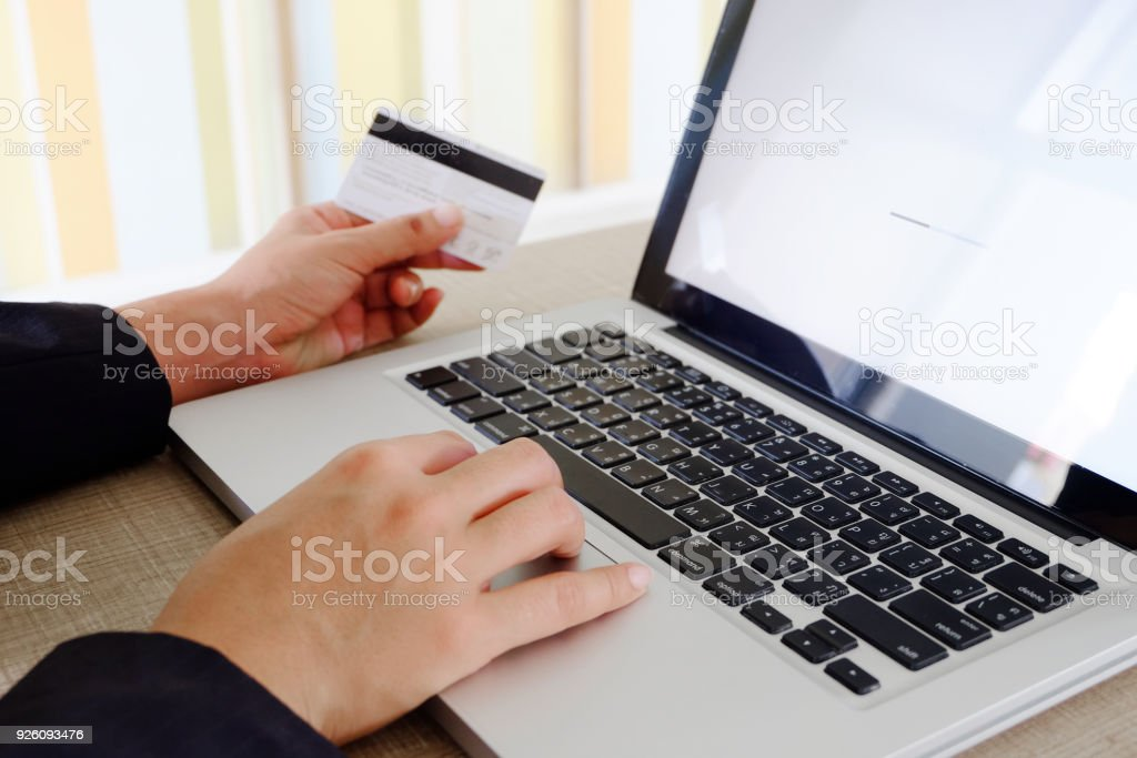 Woman hands hold Credit Cards  and use computer keyboard Notebook .online shopping concept stock photo