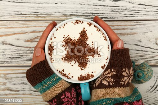 Close up two woman hands hold and hug big full cup of latte cappuccino coffee with star shaped chocolate on milk froth over white wooden table, elevated top view, directly above