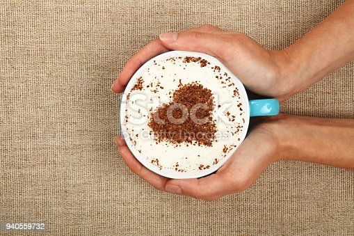 Close up two woman hands hold and hug big full cup of latte cappuccino coffee with heart shaped chocolate on milk froth over canvas tablecloth, elevated top view, directly above