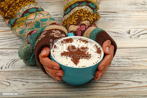 Close up two woman hands hold and hug big full cup of latte cappuccino coffee with star shaped chocolate on milk froth over white wooden table, high angle view