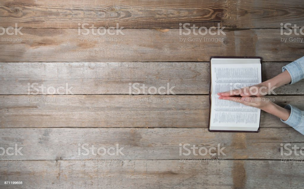 Woman hands holding a bible over a desk. She is reading and paying. Overhead point of view stock photo