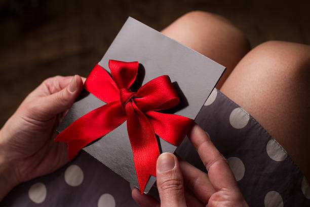 woman hands holding a black paper card with red ribbon - gutscheinkarten stock-fotos und bilder