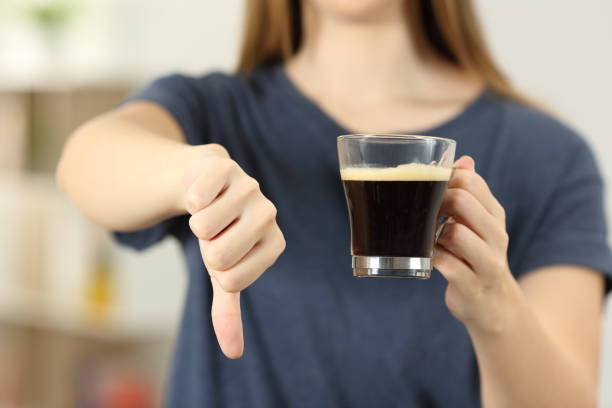 Woman hands holding a coffee cup with thumbs down Front view close up of a woman hands holding a coffee cup with thumbs down at home caffeine stock pictures, royalty-free photos & images