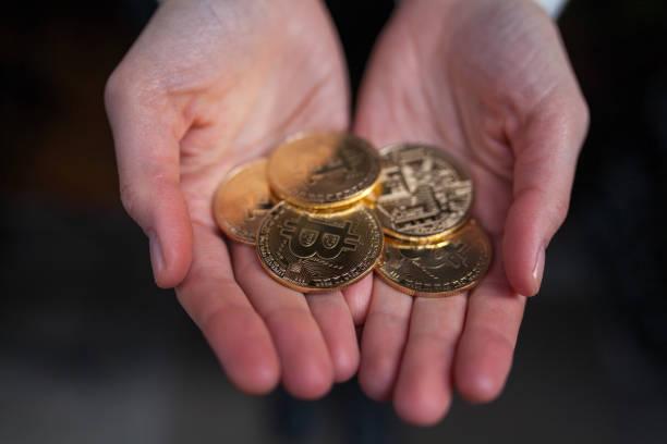 mains de femme tenant un grand nombre de pièces de monnaie bitcoin, vue de dessus - éther photos et images de collection