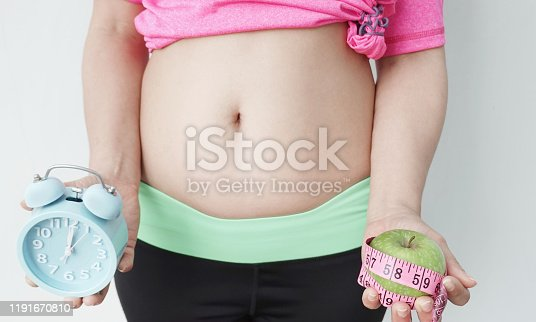 istock Woman Hands  holding Alarm clock and green apple Measuring Fat Belly which she feeling  gain weight,sport, fitness and diet concept 1191670810