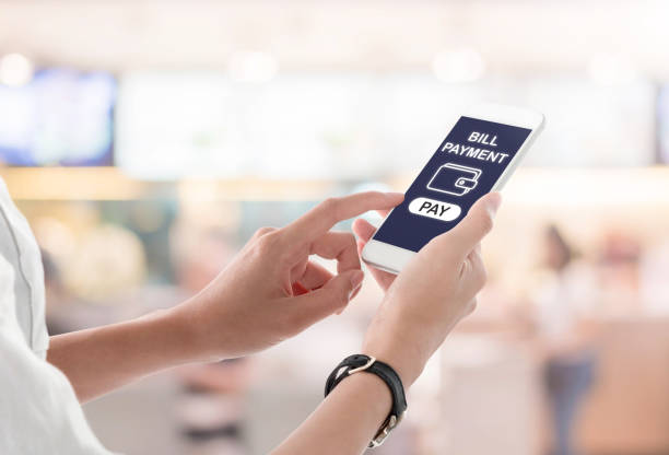 Woman hands holding and using smartphone with bill payment screen, wallet icon and pay button on blurred shopping mall background. Mobile payment concept. stock photo