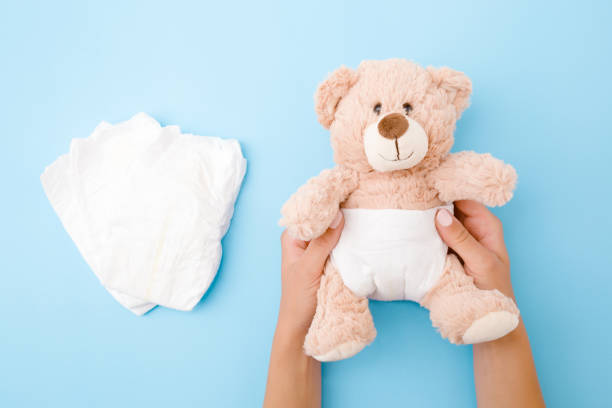 Woman hands holding brown teddy bear with white diaper on pastel blue background. Closeup. Top view. Woman hands holding brown teddy bear with white diaper on pastel blue background. Closeup. Top view. little girls in panties stock pictures, royalty-free photos & images