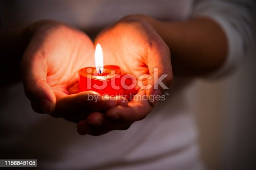 Woman hands holding burning heart-shaped candle. Symbol of hope, peace and love.
