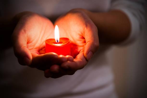 Frauenhände halten brennende herzförmige Kerze – Foto