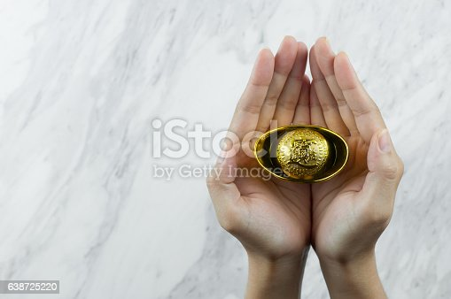 Woman hands holding chinese gold Ingot on white marble Background. copy spcae.
