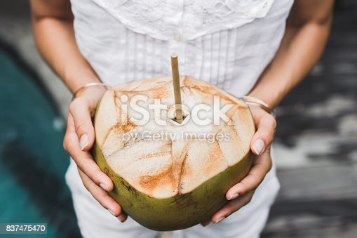 istock Woman hands holding cold and fresh young coconut. Bali tropical mood 837475470