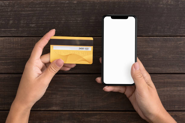 Woman hands holding credit card and using cell phone Online payment. Woman hands holding credit card and using cell phone for financial transaction. New generation gadget phone charging stock pictures, royalty-free photos & images