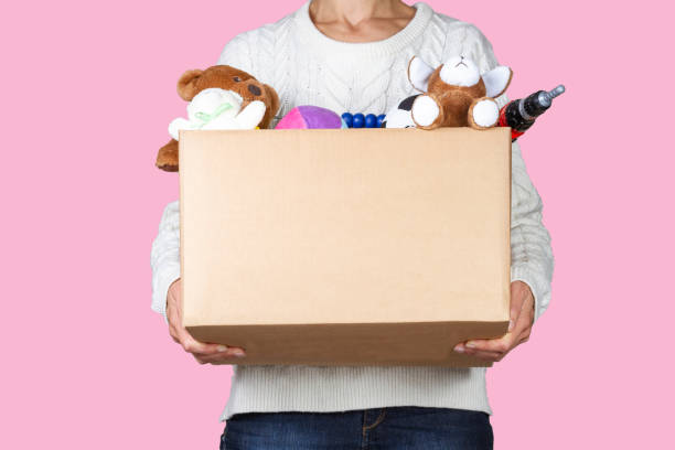 Woman hands holding donation box with clothes, toys and books Woman hands holding donation box with clothes, toys and books. kids cleaning up toys stock pictures, royalty-free photos & images