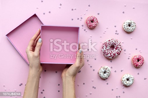 Woman hands holding empty box. Pink background with donuts.