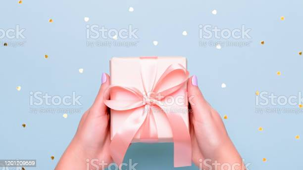 Woman hands holding gift box in pink color on pastel blue background picture id1201209559?b=1&k=6&m=1201209559&s=612x612&h=niy pxir c9zxa0kgdqiht7b3gyq99hwxbc6 mdtln8=