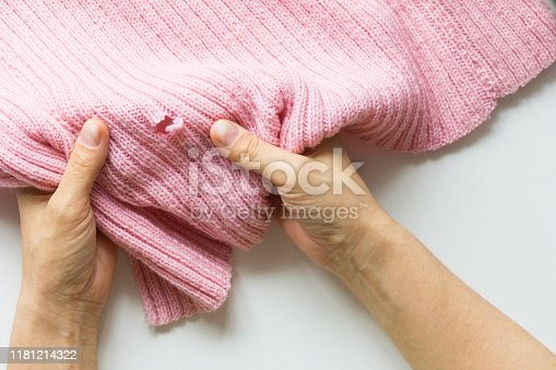 Woman hands holding the knitted thing with hole made by mole