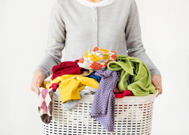 Woman hands holding laundry basket stock photo
