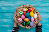 Woman hands holding nest with Easter eggs