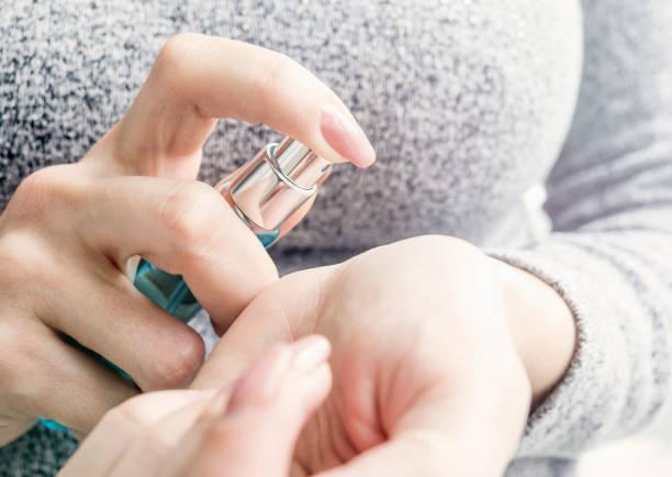 woman hands holding perfume - spruzzo profumo foto e immagini stock