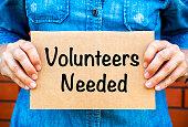 istock Woman hands holding piece of cardboard with words Volunteers Needed 1087246444