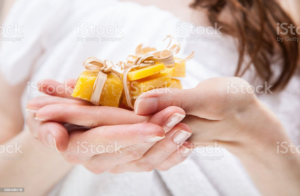 Woman hands holding pieces of beeswax stock photo
