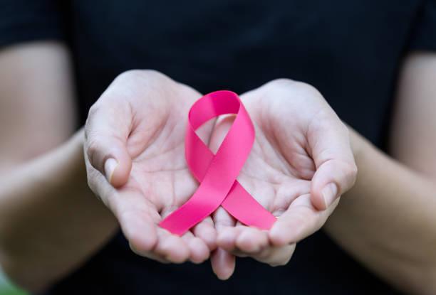 mãos de mulher segurando uma fita rosa para apoiar a campanha de mês de conscientização de câncer de mama. - outubro rosa - fotografias e filmes do acervo
