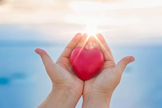 Frau Hände halten rotes Herz bei Sonnenuntergang – Foto