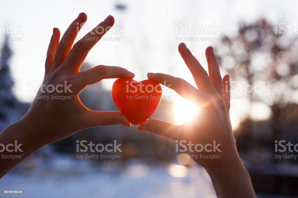 Manos de mujer con corazón rojo al atardecer - foto de stock