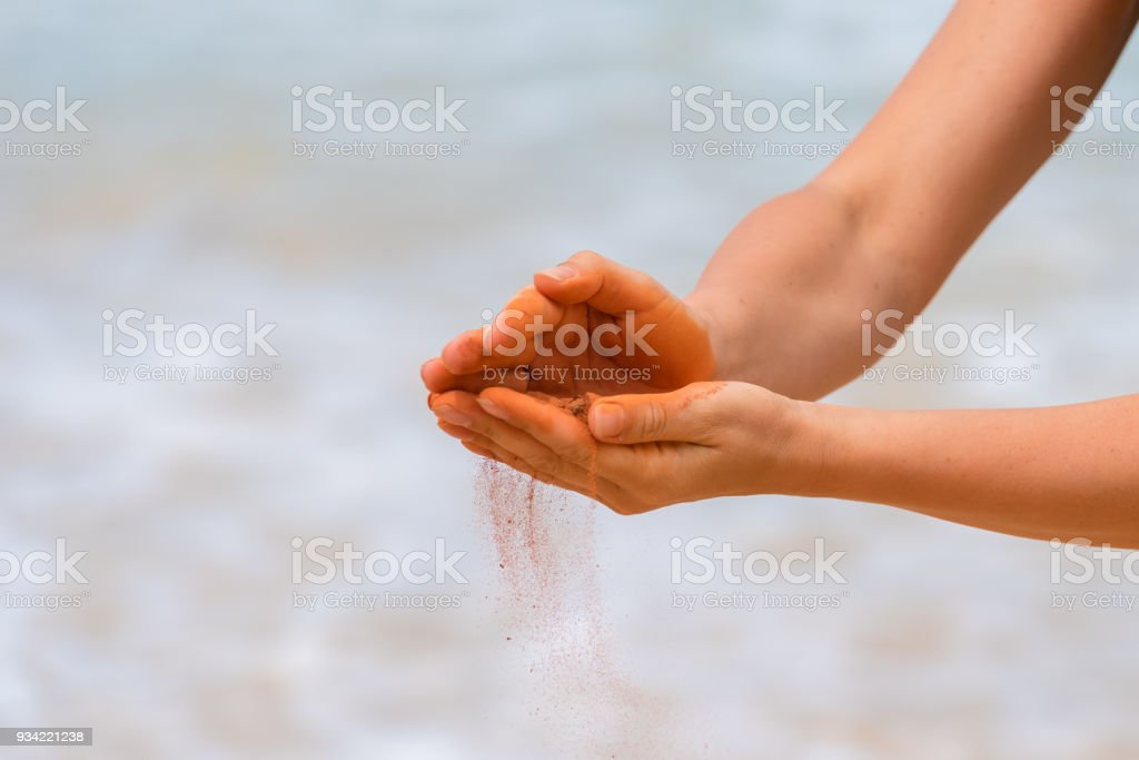 Woman hands holding red sand on the beach in aboriginal art style stock photo