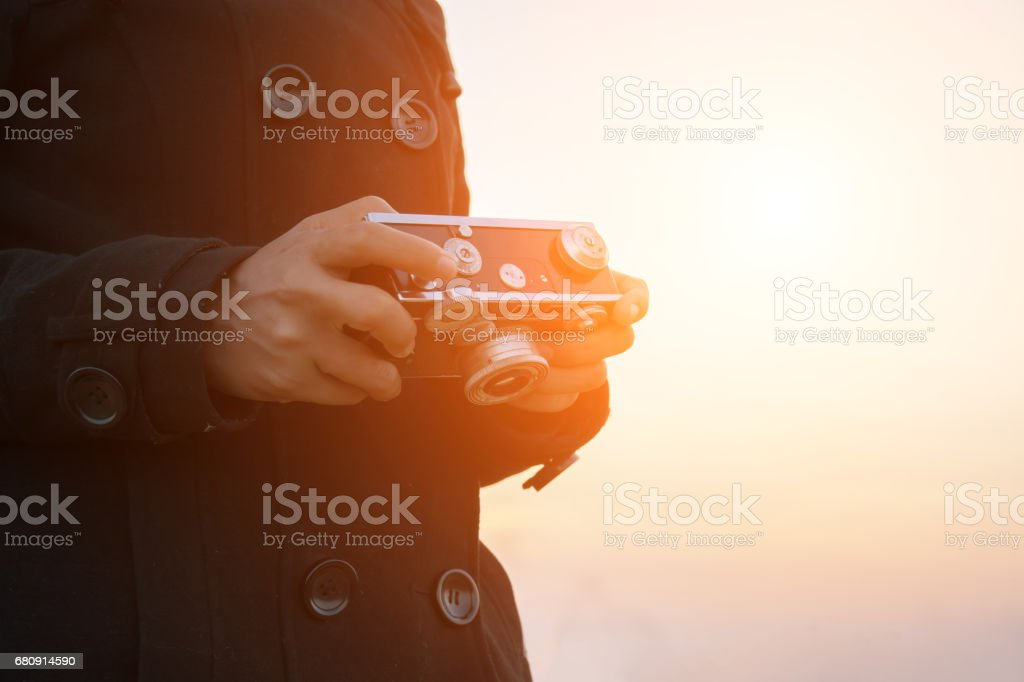 Woman hands holding retro camera with the black coat royalty-free stock photo