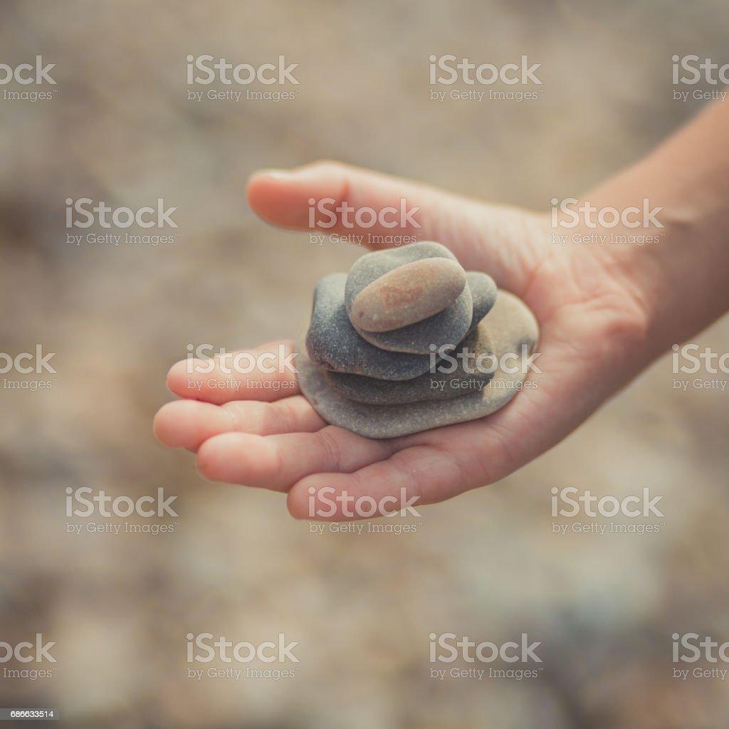 Frau die Hände halten Steinchen in Hand am Strand Hintergrund mit brennenden Sonne Lizenzfreies stock-foto