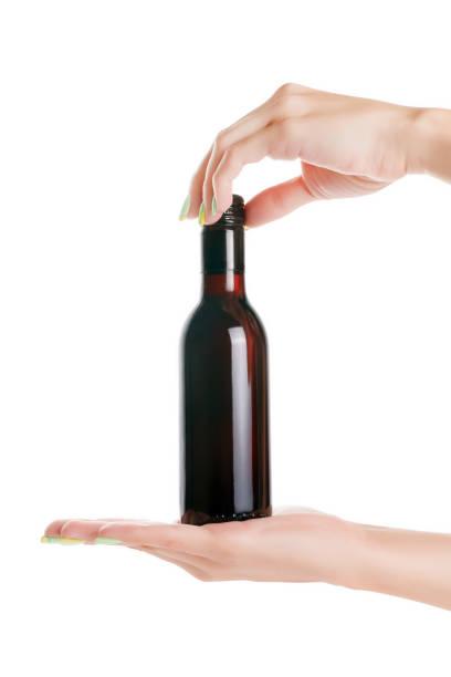 frau hände halten kleine weinflasche. isoliert mit beschneidungspfad - mini weinflaschen stock-fotos und bilder