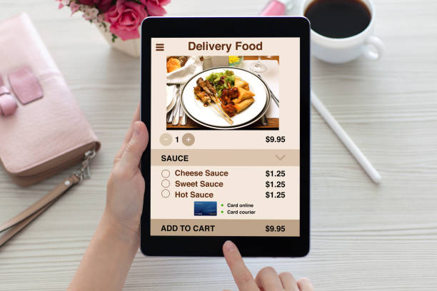 woman hands holding tablet computer with app delivery food screen - food delivery стоковые фото и изображения