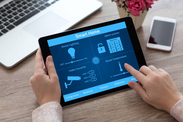 woman hands holding tablet pc computer smart home near laptop - home automation stock pictures, royalty-free photos & images