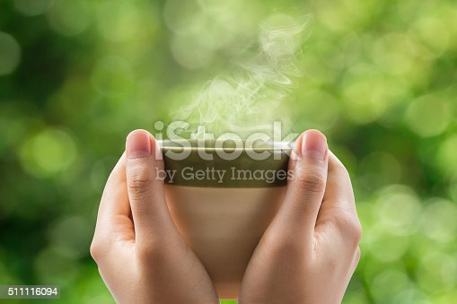 istock Woman hands holding tea cup on green bokeh background. 511116094