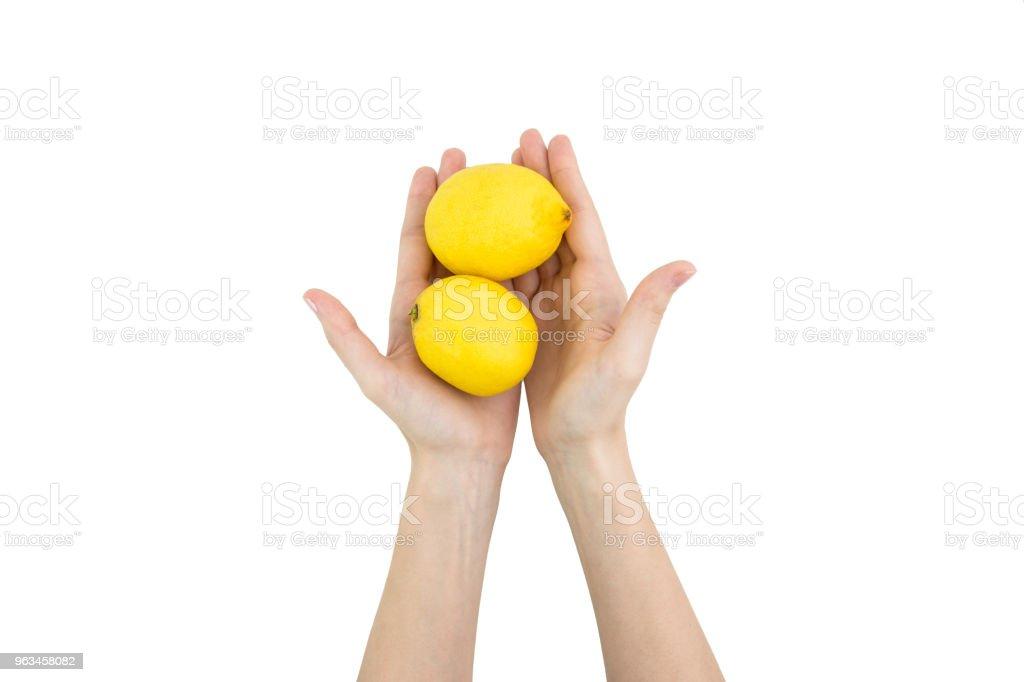 Kvinna händer som håller två färska citroner isolerad på vit bakgrund - Royaltyfri Bulgarien Bildbanksbilder