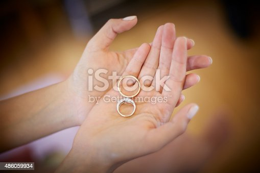 Woman hands holding two engagement rings, one gold one silver. The young woman has her nails done (French Manicure). The background is out of focus to keep all the attention to the main scene. Photography of jewelry. Horizontal format. Shot with Canon EOS 5D.