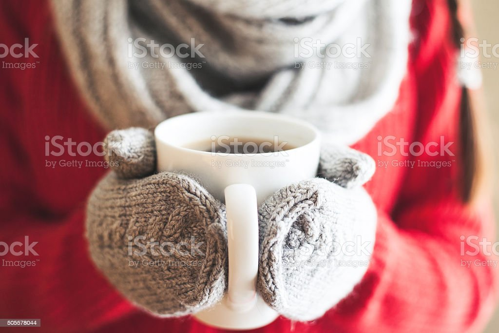 Woman hands in gloves holding a mug stock photo