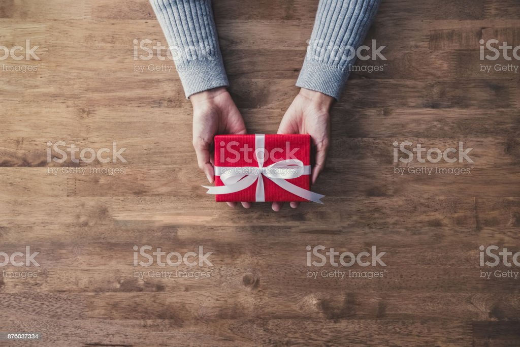 Woman hands in gray sweater on wood table giving red Christmas gift box stock photo