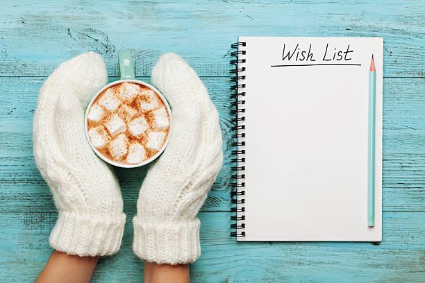 woman hands in mittens holding cocoa. christmas planning concept. - weihnachts wunschliste stock-fotos und bilder