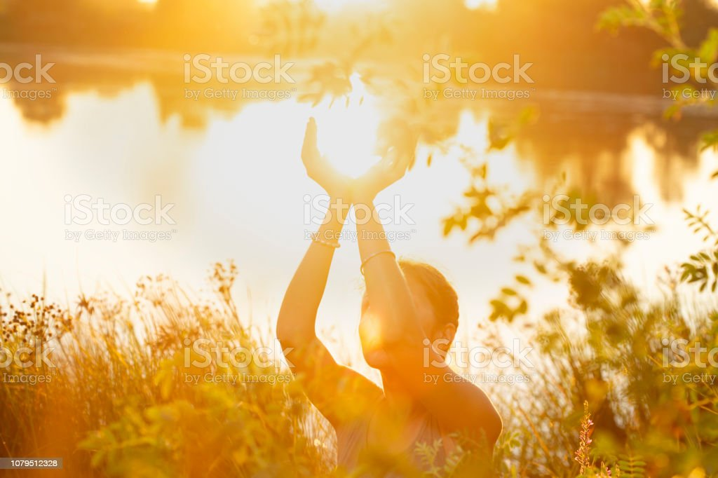 woman hands in mudra like in the palm of hands, at sunset  on the lake in nature - Royalty-free Bell Stock Photo